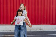 Sisters standing in front of a red wall - ERRF01629