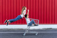 Sisters with shopping cart in front of red wall - ERRF01632