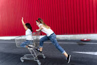 Sisters with shopping cart in front of red wall - ERRF01635