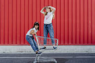 Sisters with shopping cart in front of red wall - ERRF01638
