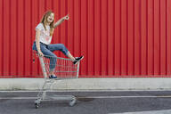 Girl in a shopping cart in front of red wall - ERRF01644