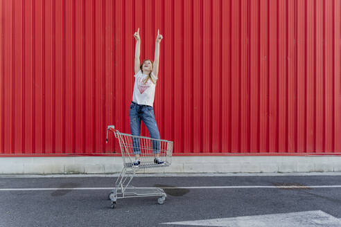 Girl in a shopping cart pointing fingers up in front of red wall - ERRF01647