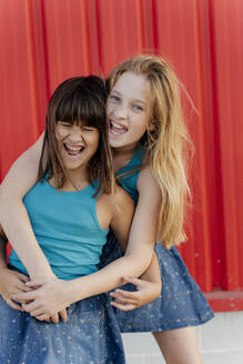 Sisters hugging in front of a red wall - ERRF01662