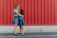 Sisters hugging in front of a red wall - ERRF01665