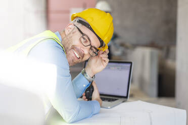 Architect using laptop at construction site, looking at camera - ZEF16155