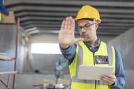 Architect using laptop at construction site - ZEF16158