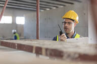 Architect using walkie talkie and laptop at construction site - ZEF16161