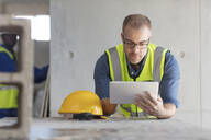 Architect using laptop at construction site - ZEF16164