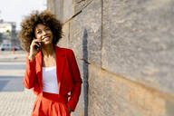 Portrait of smiling young woman on the phone wearing fashionable red pantsuit - GIOF06871