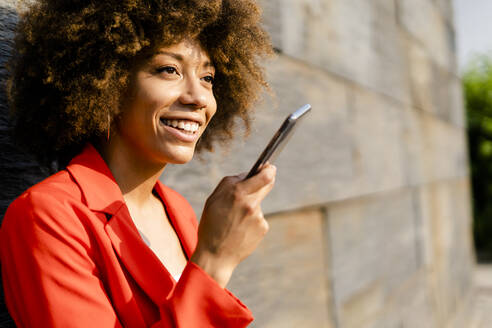 Portrait of smiling young woman on the phone wearing fashionable red suit jacket - GIOF06874