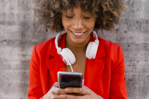 Portrait of smiling young woman with headphones using smartphone - GIOF06877