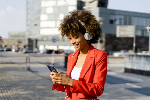 Smiling young woman with headphones wearing fashionable red pantsuit looking at smartphone - GIOF06880
