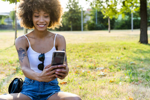 Portrait of tattooed young woman  taking selfie with smartphone in summer - GIOF06907
