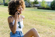 Portrait of happy young woman on the phone sitting on a meadow - GIOF06913