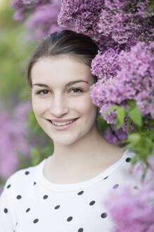 Deutschland, Jerichower Land, Gommern: Porträt einer jungen lächelnden Frau im Frühling vor einem Fliederbusch - JESF00238