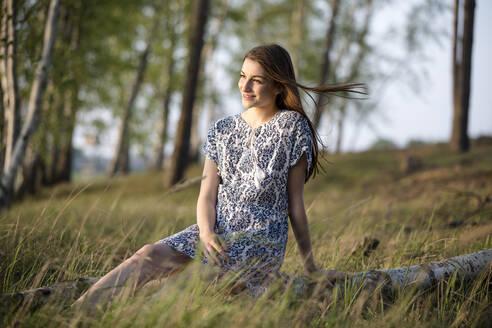 Deutschland, Jerichower Land, Gommern: Junge Frau sitzt auf einem Baumstamm im Birkenwald und schaut in den Sonnenuntergang - JESF00250