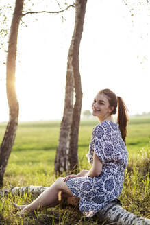 Smiling young woman sitting on a tree trunk and enjoying sunset - JESF00253