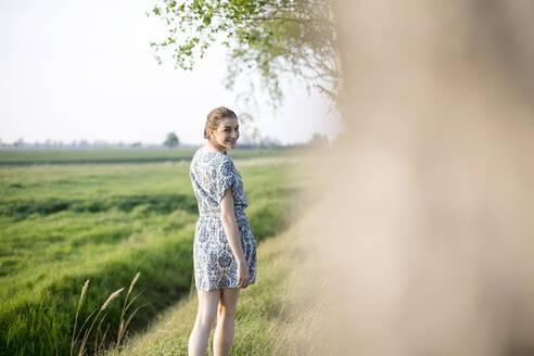 Deutschland, Jerichower Land, Gommern: Junge Frau im Kleid läuft in einem Birkendwald entlang und sucht Entspannung - JESF00256