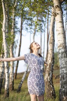 Deutschland, Jerichower Land, Gommern: Junge Frau im Kleid läuft in einem Birkendwald entlang und erfreut sich an der Natur - JESF00259
