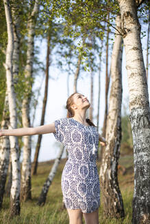 Smiling young woman enjoying nature in a forest - JESF00259