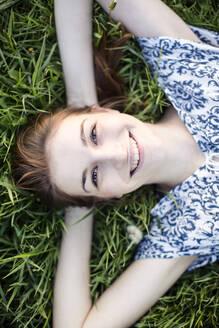 Deutschland, Jerichower Land, Gommern: Junge Frau liegt im Kleid lächelnd auf einer Frühlingswiese und genießt die Natur - JESF00265