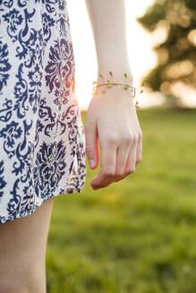 Deutschland, Jerichower Land, Gommern: Frau steht im Sonnenuntergang in der Natur auf einer Wiese und hat Hirtentäschel als Armband um den Arm - JESF00268