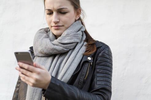 Deutschland, Jerichower Land, Gommern: Junge Frau hat Smartphone in der Hand und schaut grimmig darauf - JESF00271