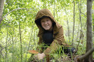 Portrait of smiling boy collecting mushrooms in the woods - VPIF01397