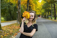 Portrait of laughing woman with bunch of autumn leaves on avenue - JUNF01677