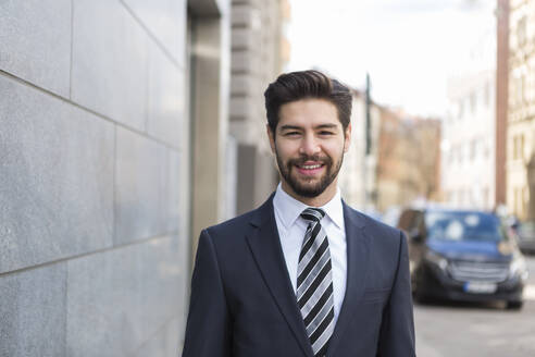 Portrait of bearded young businessman wearing blue suit jacket and tie in the city - JUNF01689