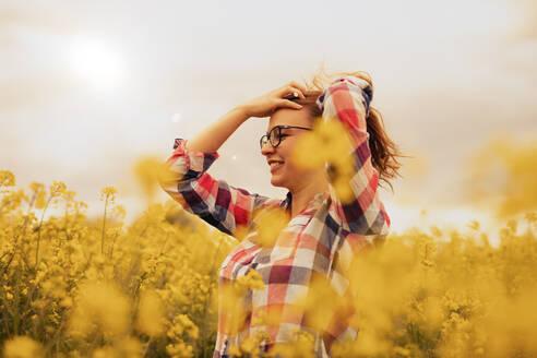 Feldweg, Deutschland, Baden-Württemberg, Nürtingen, junge Frau mit Brille lächelnd in einem blühenden Rapsfeld, Freude und Zufriedenheit - SEBF00111