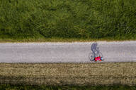 Triathlete riding bicycle on country road, Germany - STSF02140