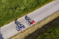 Triathletes riding bicycle on country road, Germany - STSF02143
