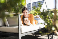 Young woman lying on couch on terrace using cell phone and laptop - UUF18244