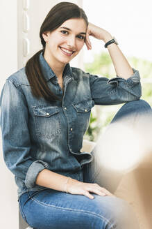 Portrait of smiling young woman wearing denim shirt at home - UUF18265
