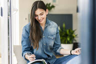 Smiling young woman wearing denim shirt taking notes at home - UUF18268