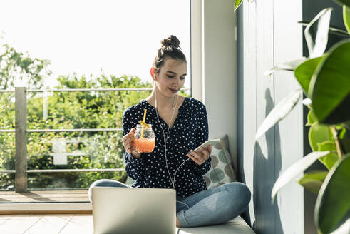 Smiling young woman with laptop, cell phone and healthy drink at home - UUF18274