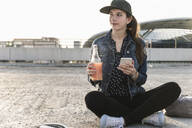Young woman with drink and cell phone sitting on parking deck at sunset - UUF18313