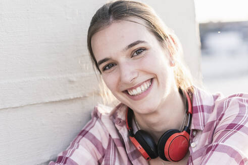 Portrait of smiling young woman with headphones - UUF18325