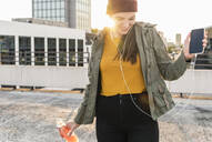 Happy young woman with earphones dancing on parking deck at sunset - UUF18328