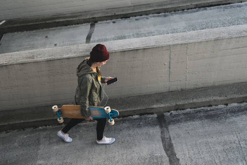 Stylish young woman with skateboard and cell phone walking on parking deck - UUF18343