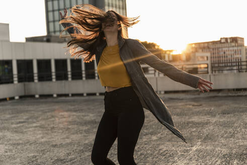 Cheerful young woman dancing on parking deck at sunset - UUF18346