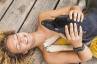 Husky shepherd mongrel dog and his mistress lying on wooden board - TCF06151
