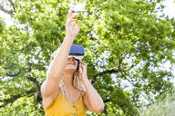 Young blond woman using virtual reality glasses outdoors - TCF06157