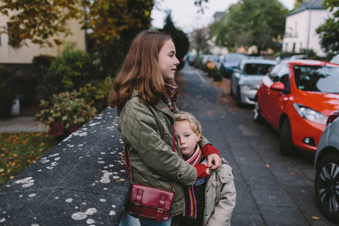 Portrait of sad sister being embraced by her sister while standing on walkway - OGF00077