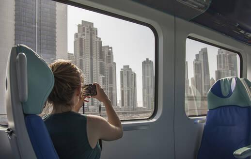 Caucasian woman photographing Dubai cityscape on train, Dubai Emirate, United Arab Emirates - BLEF11989