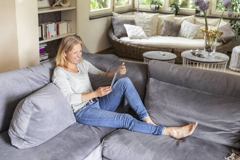 Laughing blond woman relaxing on couch at home using digital tablet - FMKF05757