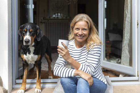 Portrait of happy mature woman sitting with coffee mug on terrace - FMKF05760