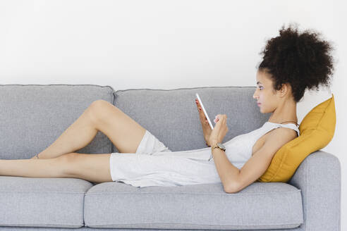Young woman using her digital tablet on the sofa. Lecco, Italy. - MRAF00408