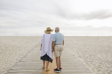 Back view of senior couple standing hand in hand on wooden boardwalk looking at horizon, Liepaja, Latvia - AHSF00695